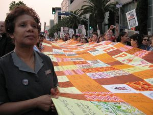 Union housekeepers carry a 60-foot long quilt. Each panel depicts a workplace injury sustained in LA's hospitality industry.